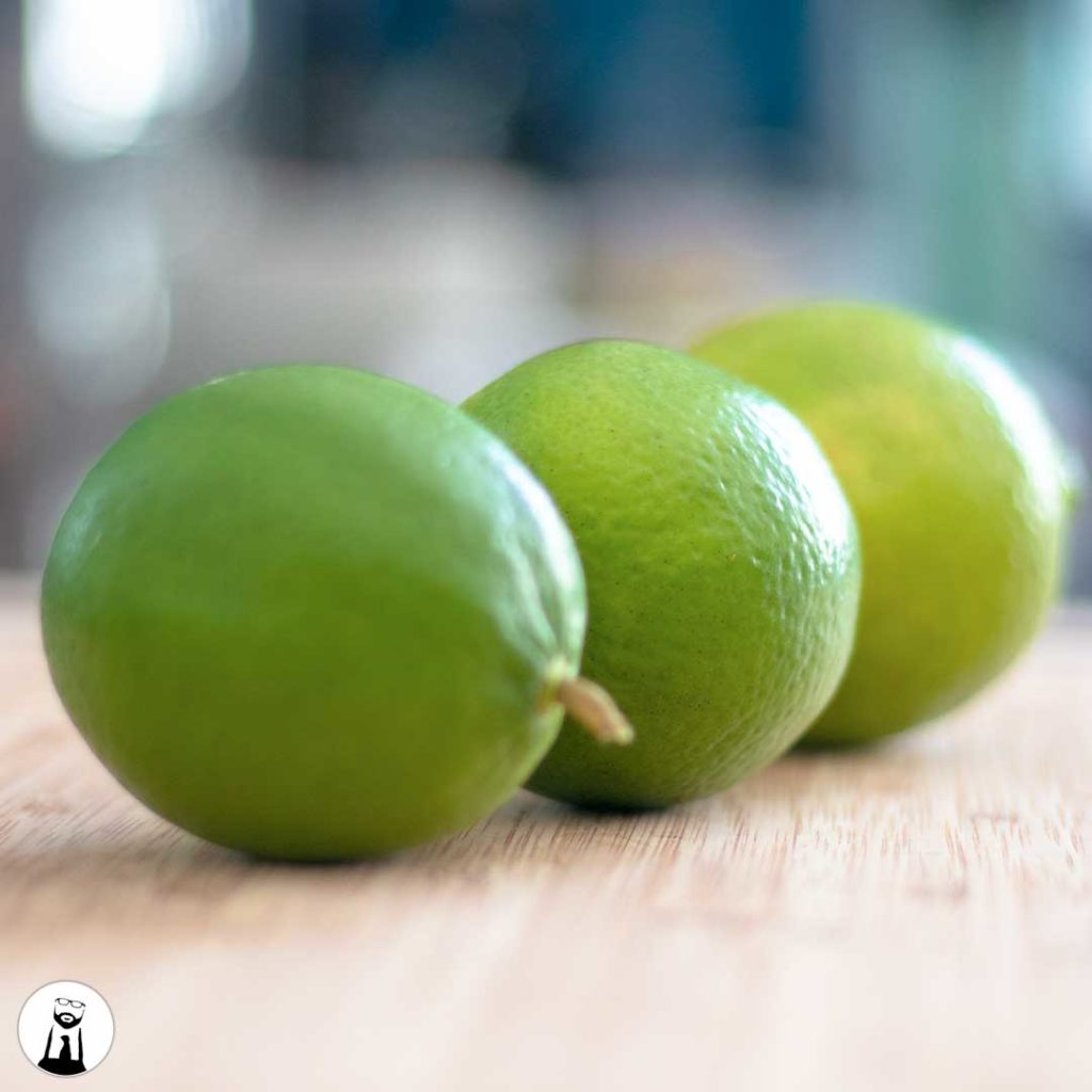 three limes on a cutting board