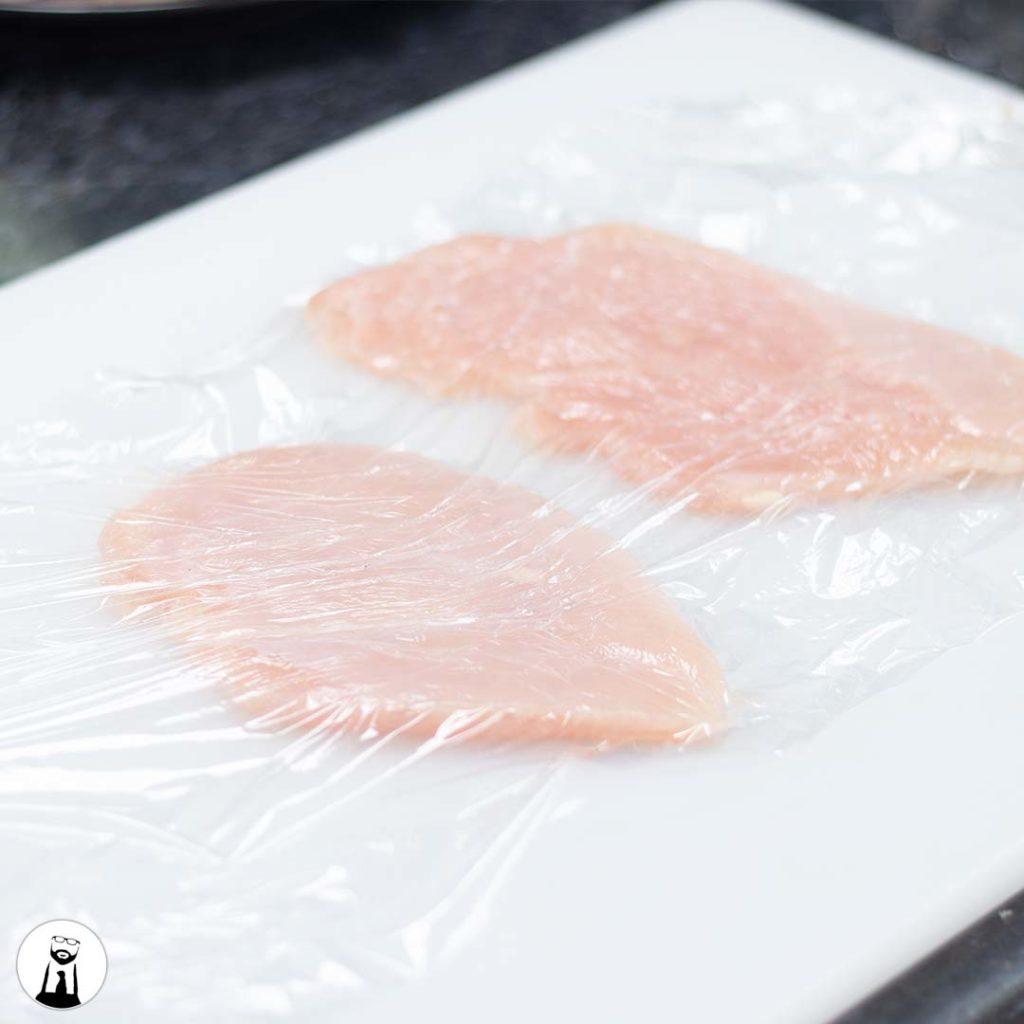Chicken breast under plastic wrap - Black Tie Kitchen
